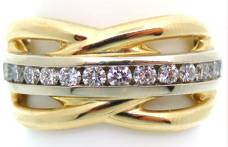 A wavy wide 14K yellow gold band with a channel around the finger holding 1.30 diamond total weight.